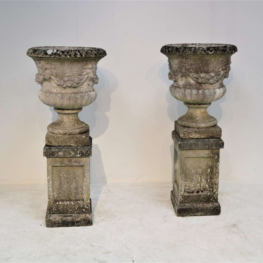 A large pair of marble di latte urns on stands
